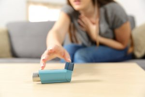 woman reaching for asthma inhaler